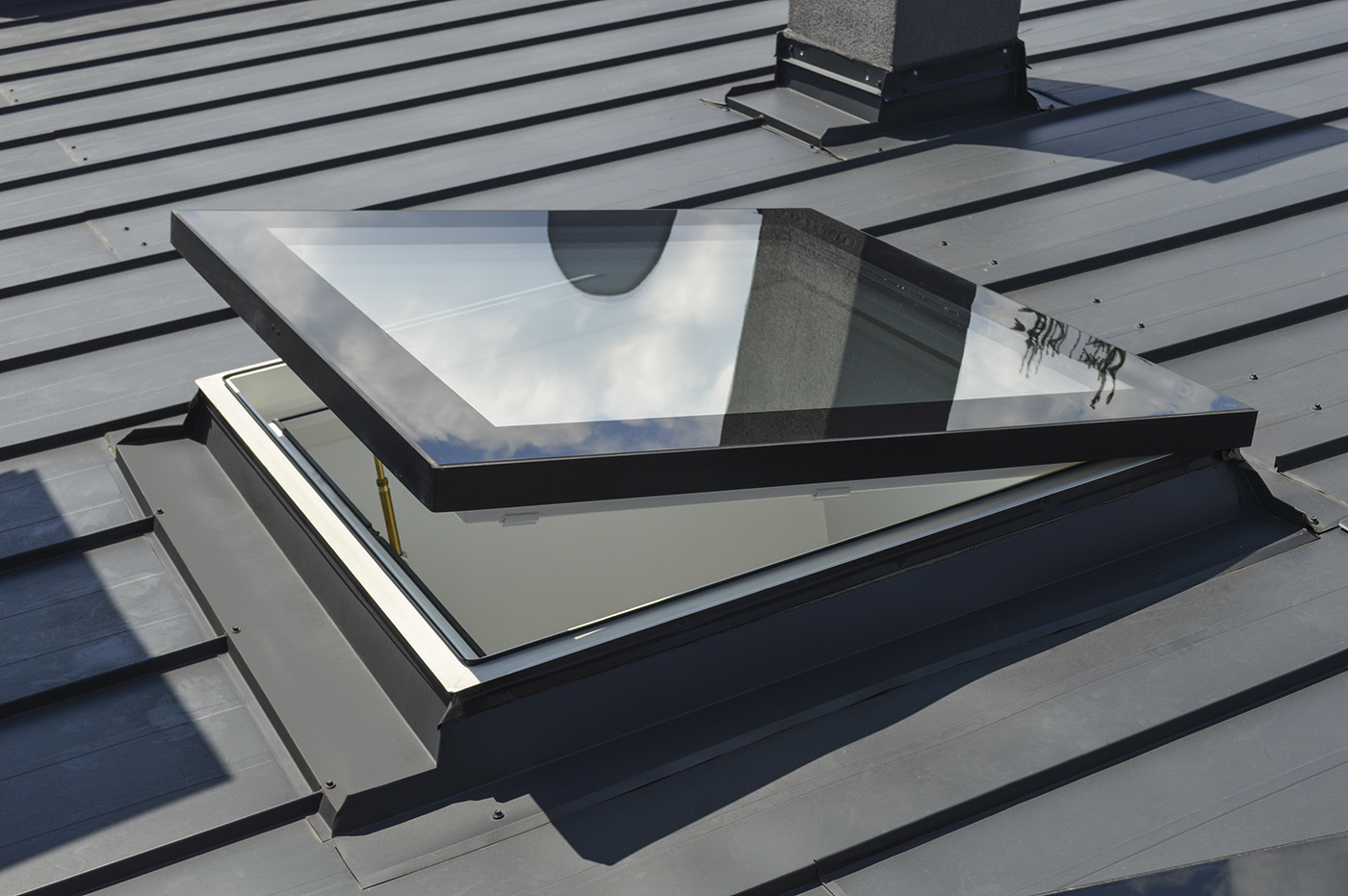 Electrically operated flat roof windows in roof
